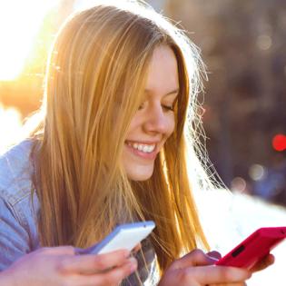 Cadaoz, jeune femme souriante chattant sur son smartphone